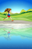 A girl running along the river Royalty Free Stock Photo