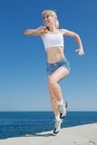 Girl is running along the seashore. Vigorous blond woman in shorts and white shirt is running outdoors Stock Photo