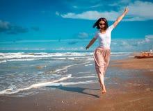 Girl running along seaside royalty free stock photography