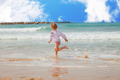 Girl running along the surf Stock Images