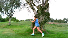 Girl running around a big tree Royalty Free Stock Photography