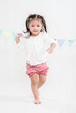 Girl Running Around on White Background. Healthy and happy girl running on white background with triangle flags Stock Images