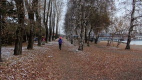 Girl running in autumn park during cold cloudy day. Woman exercising outdoors