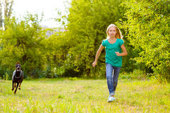 Girl running away from dog or doberman in summer Stock Photography