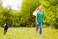 Girl running away from dog or doberman in summer Royalty Free Stock Images