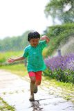 Girl running away from water droplets Royalty Free Stock Photo