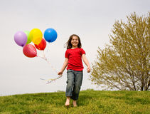 Girl Running With Balloons. Little Girl Running Down a Hill With Balloons Stock Images