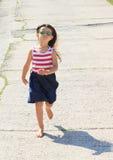 Girl running barefoot Stock Images