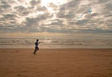 Girl running on a beach. Girl running along the water edge Royalty Free Stock Photography