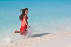 Girl running on the beach. Girl in a red dress with long flowing hair running down the beach to the water Royalty Free Stock Photo