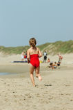 Girl running on beach. Little girl is running along the beach in the summertime on the north sea in norway Royalty Free Stock Image