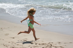 Girl running on beach. Young girl running to play in the ocean stock photography