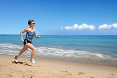 Girl running on the beach. Young woman running alone on the beach Royalty Free Stock Images
