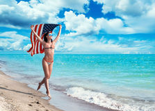 Girl running on the beach with the American flag Stock Images