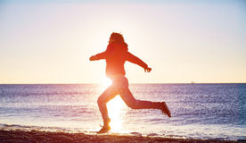 Girl running on the beach Stock Image