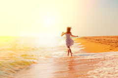 Girl running on the beach Stock Images