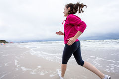 Girl running on beach Stock Images