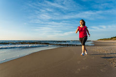 Girl running on beach Stock Photos