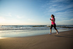 Girl running on beach Stock Photos