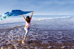 Girl running at beach with sarong Royalty Free Stock Photo