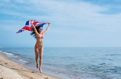 Girl running on the beach with the Union Flag. Happy young woman in bikini running on the beach with the Union Flag fluttering in her hands Stock Photos