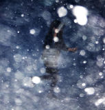 Girl running in blizzard bokeh Royalty Free Stock Photography