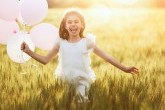 Girl running on cereal field. Happy kid is having fun on nature in the summer. Child is laughing and playing on meadow at sunset background. Girl with air stock images