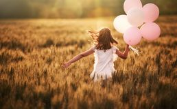 Girl running on cereal field. Happy kid is having fun on nature in the summer. Child is playing on meadow at sunset background. Girl with air balloons is running royalty free stock image