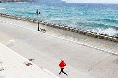 Girl running on city street at seaside Stock Photo