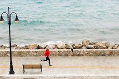 Girl running on city street at seaside Stock Images