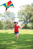 Girl running with a colorful kite outdoor smiling Royalty Free Stock Photography