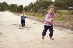 Girl Running on country lane. Girl running along country lane with boy behind and rural background Royalty Free Stock Photography