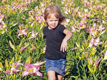 Girl running in day lilies Royalty Free Stock Photos