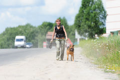 Girl running with dog. Young girl walking outdoor with her dog Royalty Free Stock Photo