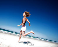 Girl running down the beach stock images