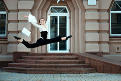 Girl running down the street tossing documents handed. Stock Photo