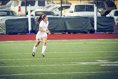 Girl running in the field. Female  playing football on varsity  soccer game Royalty Free Stock Images