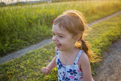 Girl running on the field  summer sunset Royalty Free Stock Image
