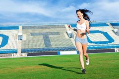 Girl running on football field Stock Photos