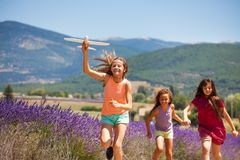 Girl running with friends and holding toy plane Stock Photography
