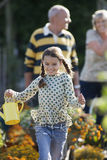 Girl (8-10) running in garden, holding watering can, smiling, grandparents standing in background royalty free stock images