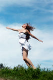 The girl running on a grass against sky Stock Photography
