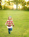 Girl running in green field at sunset Stock Photo