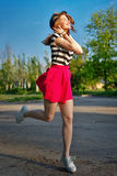 Girl running holding a hat. Royalty Free Stock Image