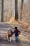 Girl running with a horse/pony. Young girl running with a horse/pony in a forest Royalty Free Stock Image