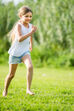 Girl running and jumping on grass Royalty Free Stock Image