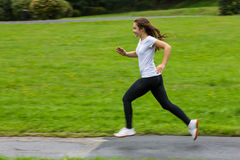 Girl running. Girl jumping on running lane in park Royalty Free Stock Photos