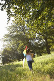 Girl running with kite in field Royalty Free Stock Image