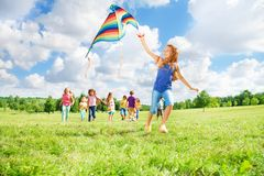 Girl running with kite with friends Royalty Free Stock Photography
