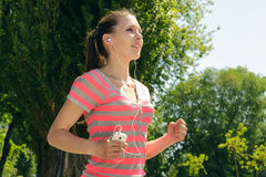 Girl while running listening to music through headphones Stock Photos